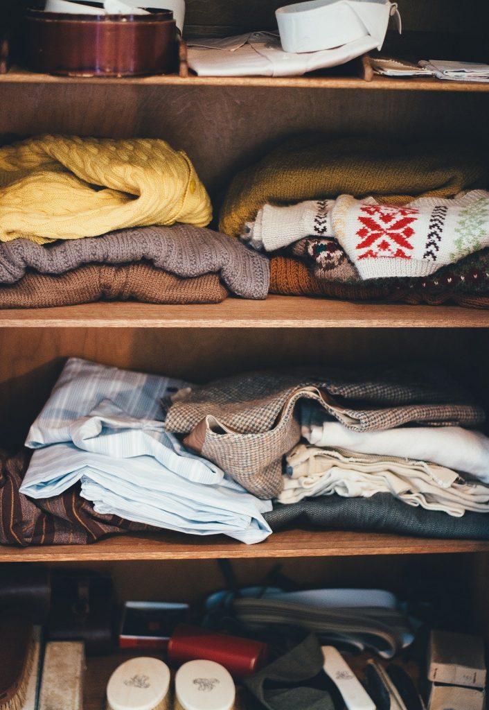 Estantes de un armario ropero con varias prendas amontonadas.